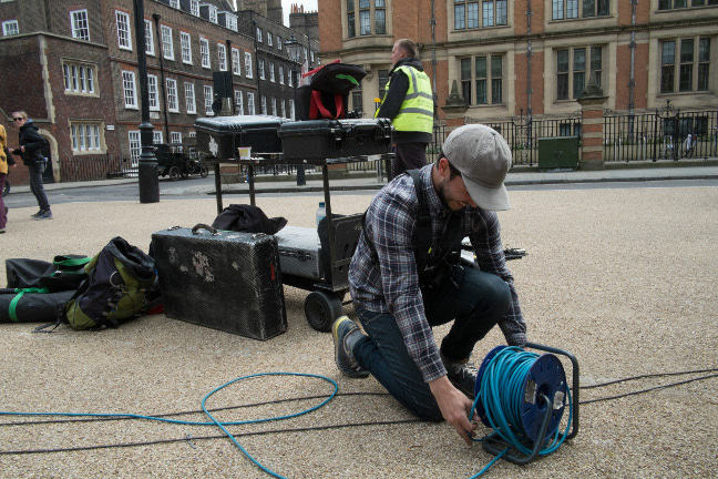 Technicians laying cables on a film set