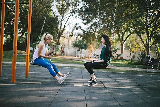 Two girls sitting on swings in a playground
