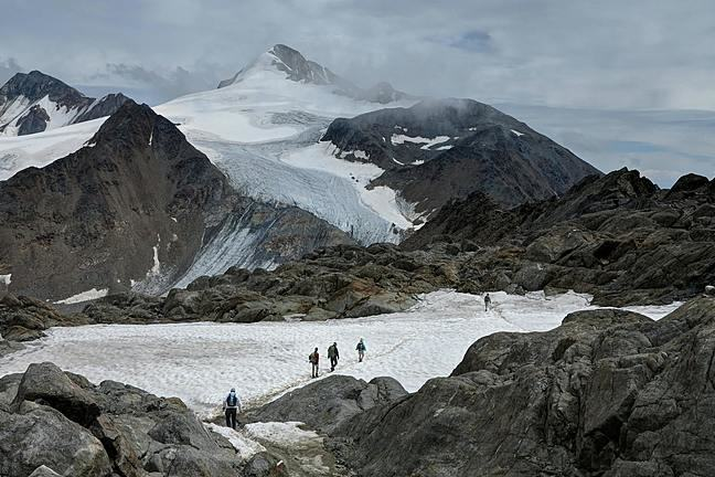 Image shows a group of people walking across a snow patch towards a glacier in the distance, surrounded by mountains.