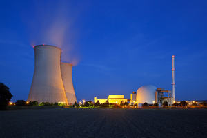 The image is of a Nuclear power station at night, two cooling towers are in shot.