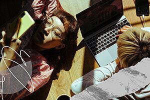 Two young people lying on the floor in the sunlight looking at a mobile phone and laptop.