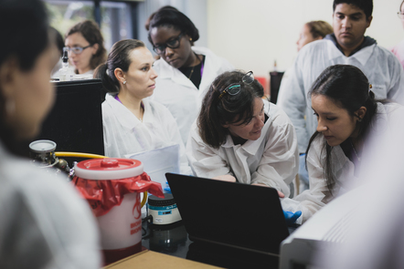 Image Accessing data - Costa Rica 2017 ACSC © Pablo Tsukayama Two women dressed in white laboratory coats, an Educator and a Learner working together on a laptop in a science lab, next to red topped disposal container and gas cylinder tube; onlookers