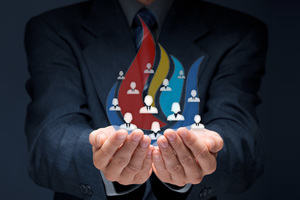 eFIRE: a businessman holding in his hands icons representing team members, surrounded by coloured flames.