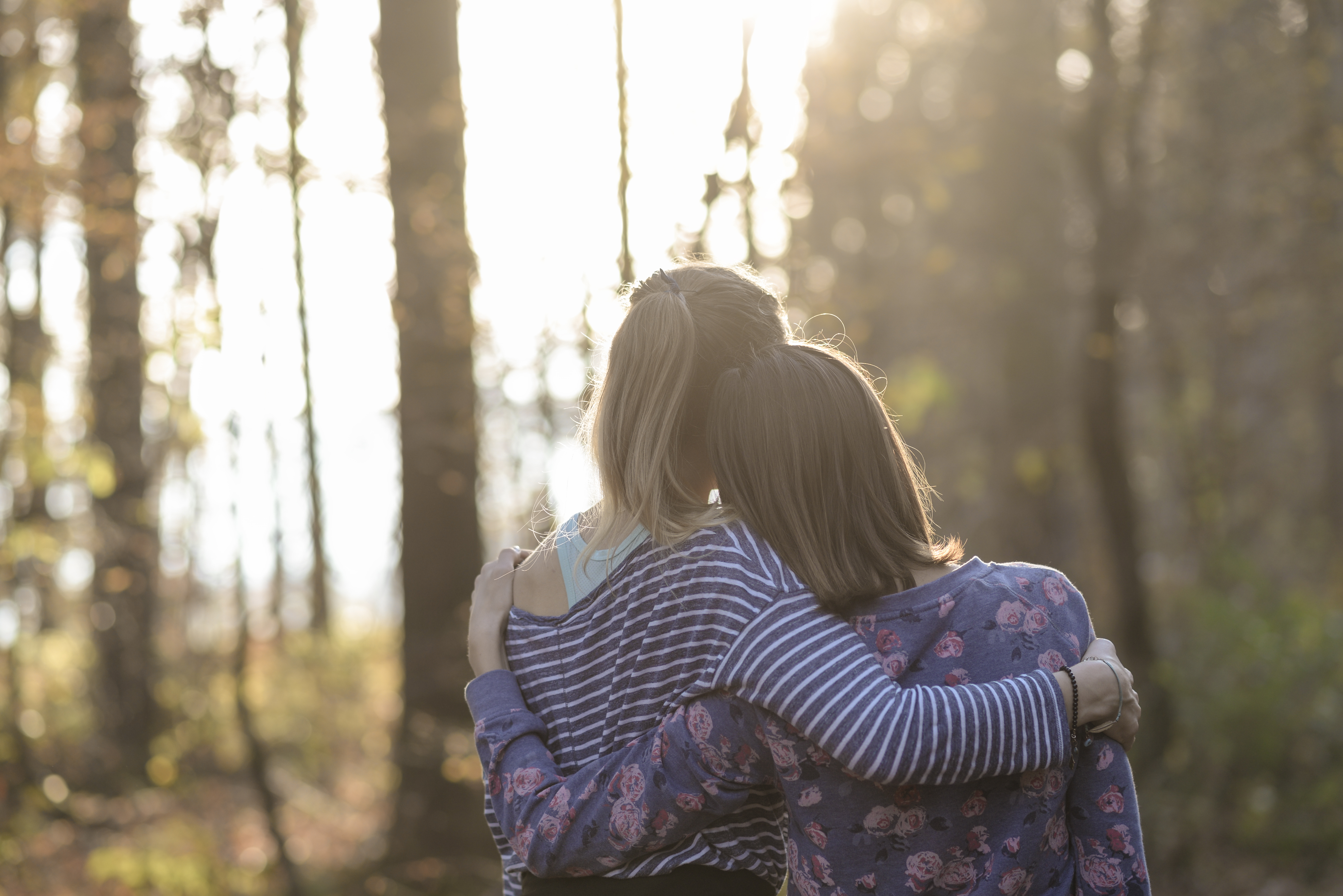 Two women walking in a forest with their arms around one another.