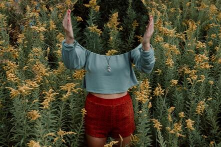 A person in a blue top and orange shorts standing in a field of flowers holding a mirror reflecting the flowers
