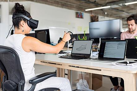 Woman using a laptop and a VR headset
