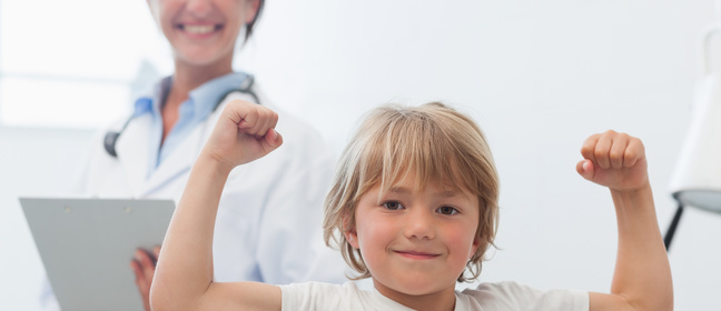 Image of smiling child showing biceps and doctor smiling in the background