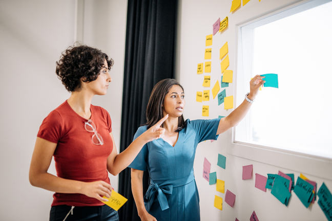 Two businesswomen are preparing presentation of project results and putting sticky notes on the wall in the seminar room.