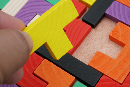 Multicolored wooden jigsaw bricks with final piece being put into puzzle