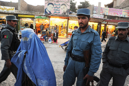 A woman in blue burka passes by policemen standing at a check point in a busy market place in Deh Afghanan.