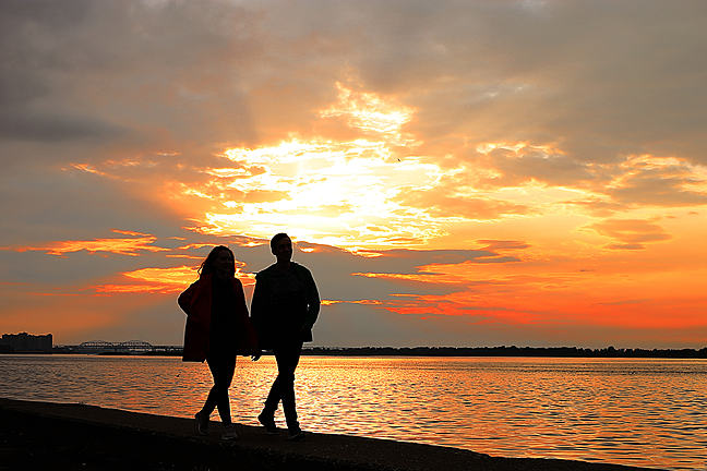 Couple walking on the beach silhouetted by sunset