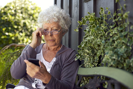 Woman with grey hair and glasses looking at the smart phone she is holding.