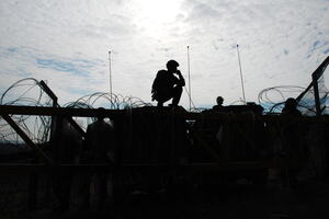 Israeli soldiers guarding a barrier, silhouetted against afternoon sun.