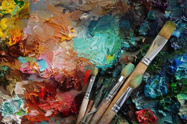 Tintas coloridas misturadas em uma paleta com pincéis de vários tamanhos.