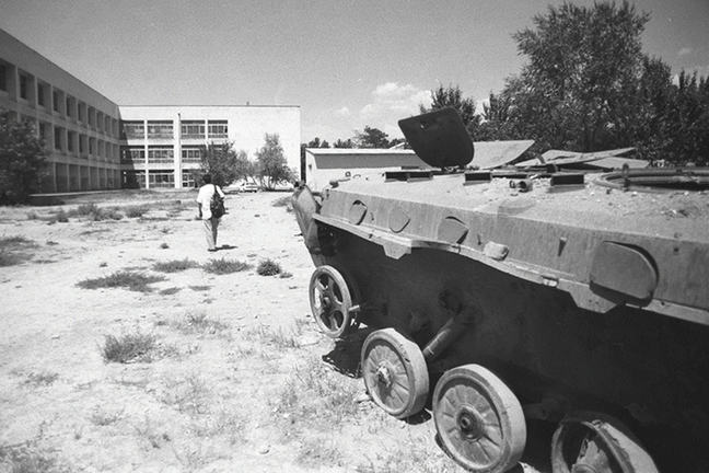 Black and white image of an old destroyed tank on a rubble-strewn campus with a student with a backpack walking away from view