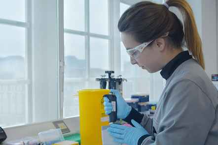 A scientist wearing safety gloves extracts liquid from a tube.