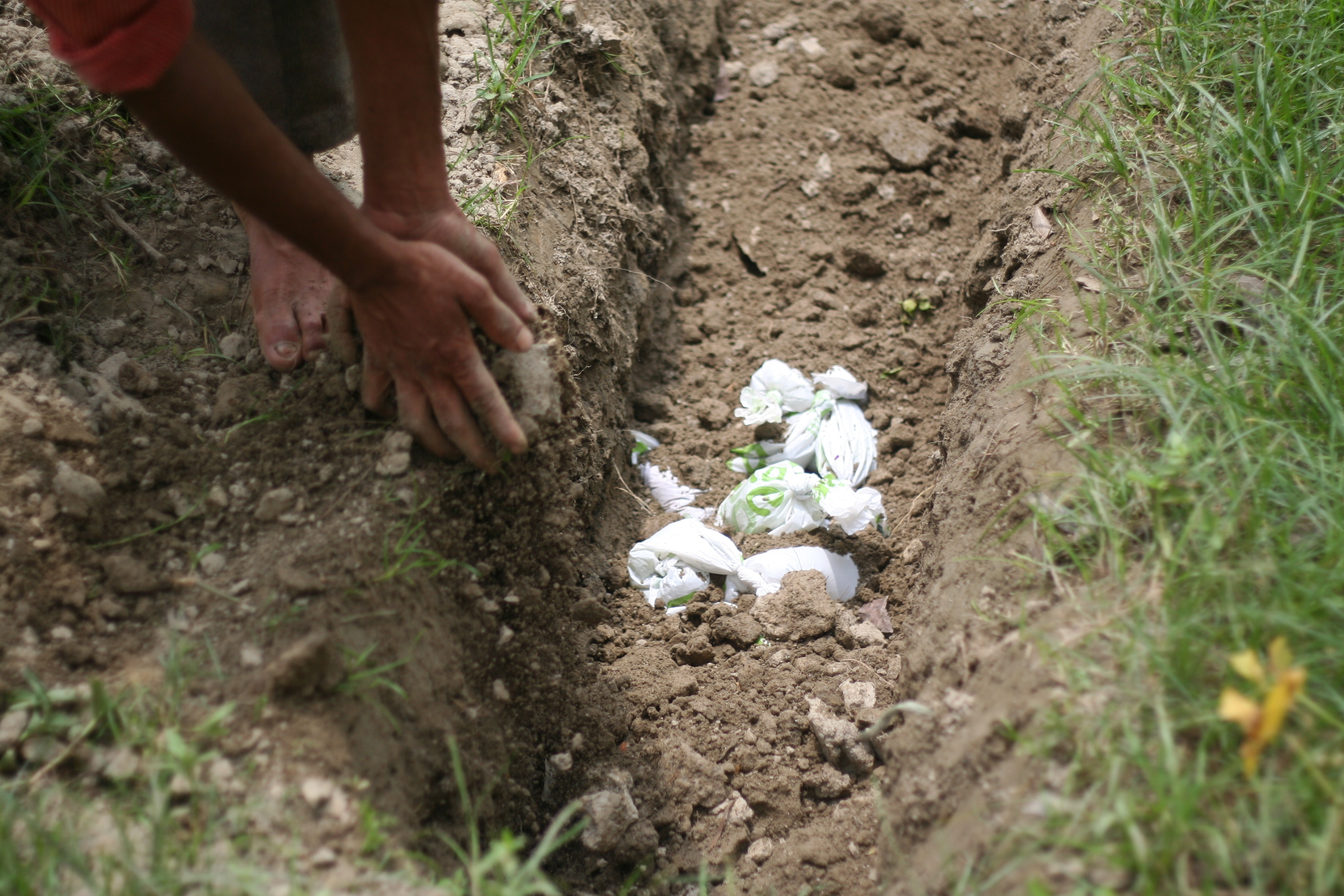 Image of waste bags being buried