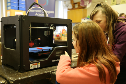 A girl working on a 3d printer while a mentor supervises.