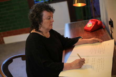 Poet Laureate Carol Ann Duffy sat at a desk writing her poetry