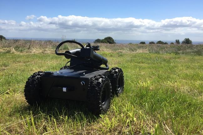 A four-wheeled robot vehicle with off-road tyres looks out across our Field Robotics site