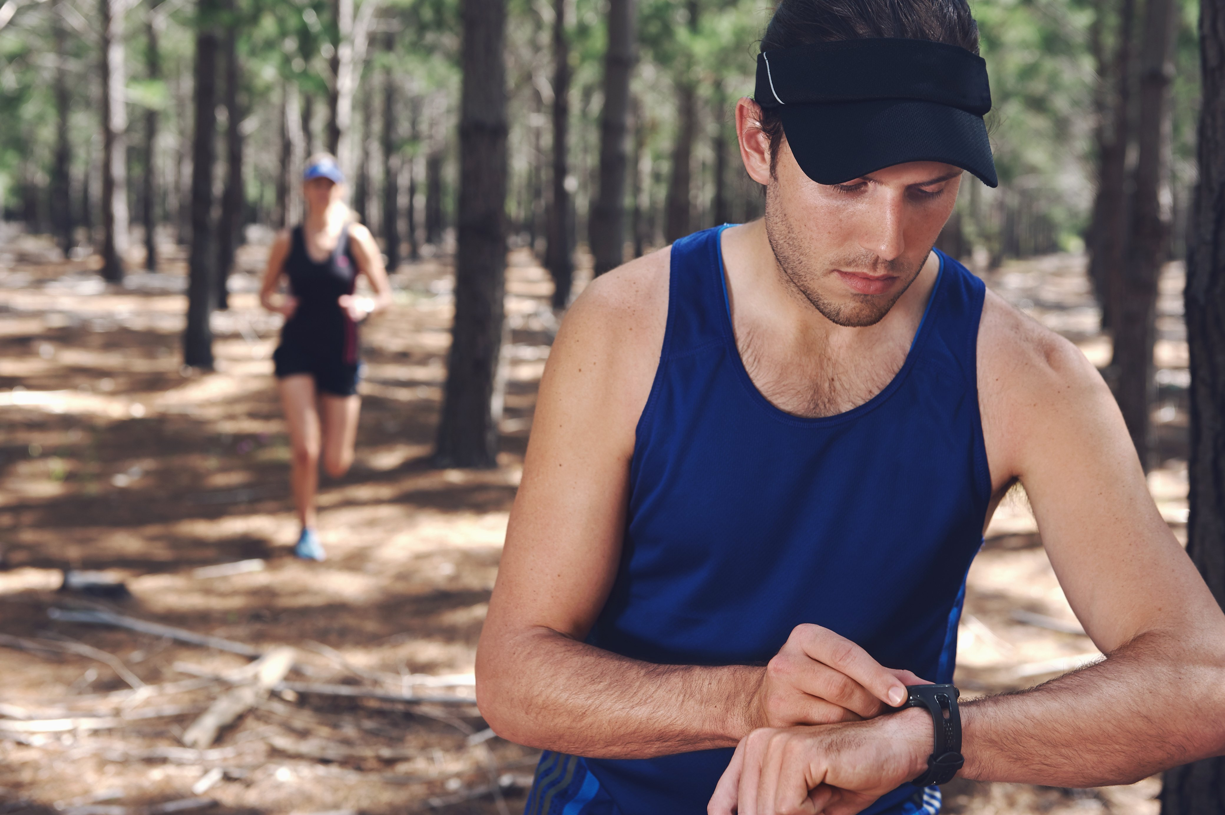 A runner in a forest checks his watch