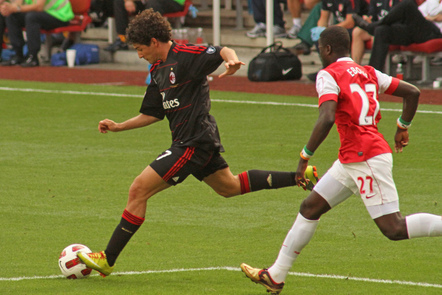 Two footballers from AC Milan and Arsenal fight for the ball