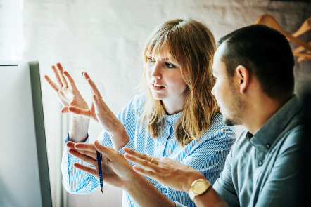 A woman and a man in discussion in front of a computer screen
