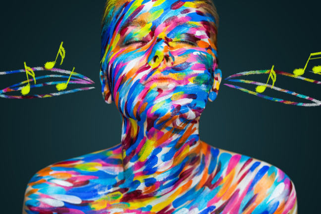 Blissed out woman covered in stripey, multi coloured paint with music notation and staff flowing through her ears