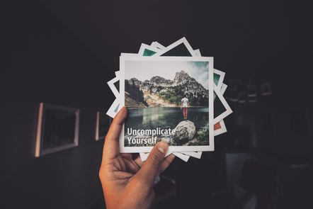 A hand holding a pile of polaroids