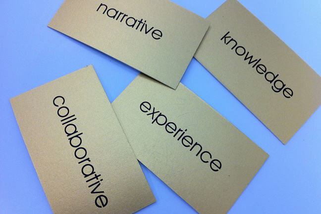 "Four metal tags with the words ""experience"", ""knowledge"", ""collaborative"", ""narrative"""