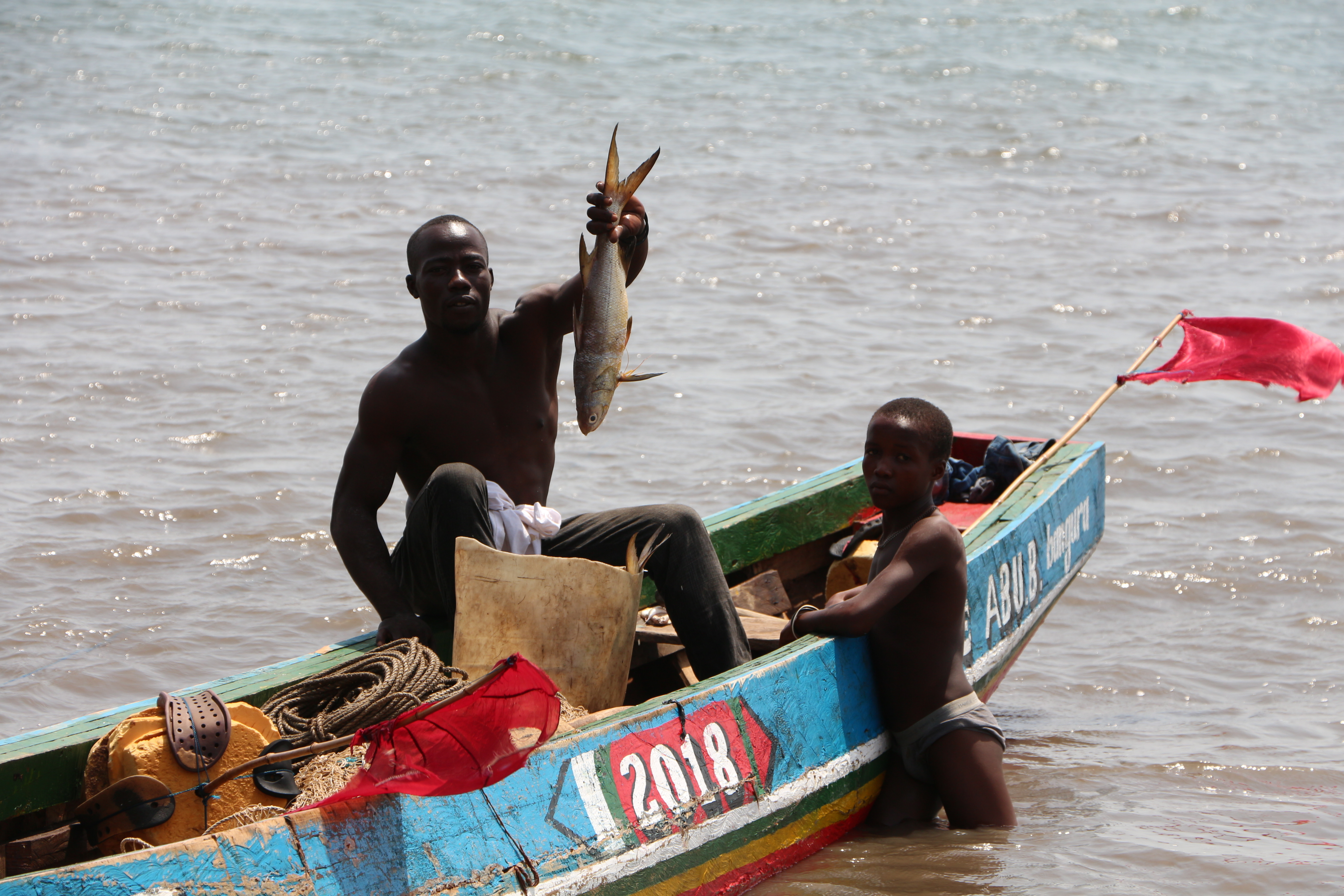 A man and youth on a blue boat, sitting in the sea. The man is holding up a fresh fish.