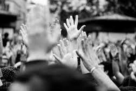 La imagen es una fotografía en blanco y negro de muchas manos levantadas. La gente parece estar en un espacio al aire libre. No podemos identificar caras o cuerpos, solo manos que muestran diferentes colores de piel.