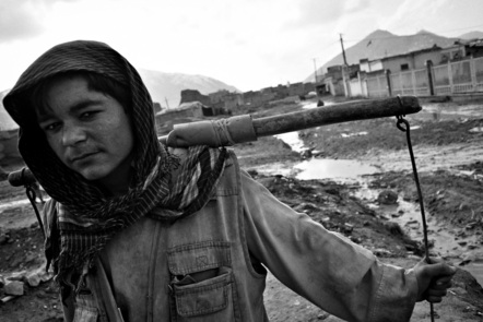 A young boy called Mohammad Madari, 15, carrying buckets.