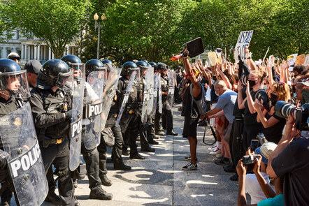 A photograph of protesters lining up against American riot police during a protest at the murder of George Floyd