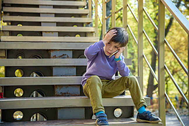 Boy sitting on outside steps with a hand to his head and the other hand holding a phone which he is looking at