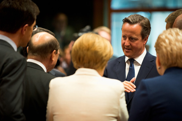 David Cameron stands talking with other European leaders in a meeting room