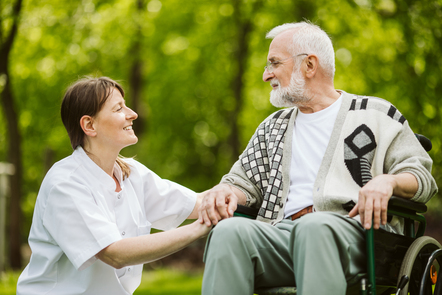 Female nurse and a male patient in a wheelchair in the garden are facing each other and smiling