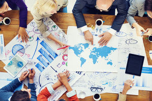 Image showing people meeting and planning using a world map