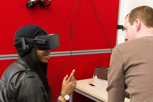 A woman in a virtual reality headset sitting a desk with a man nearby talking to her