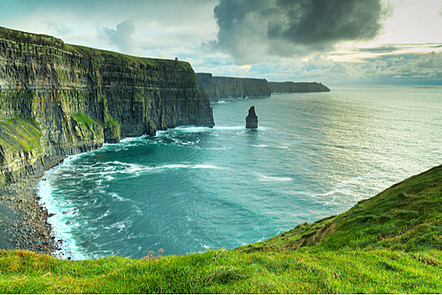 Cliffs of Moher overlooking the sea at sunset.