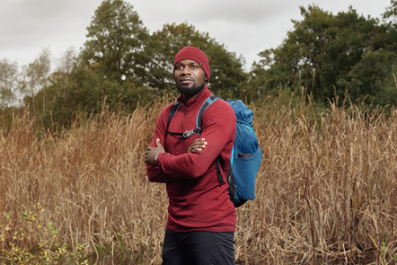 Dwayne Fields with his arms folded, stood in a field with a red jacket, hat and blue rucksack