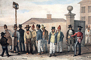 A group of convicts standing along a wall