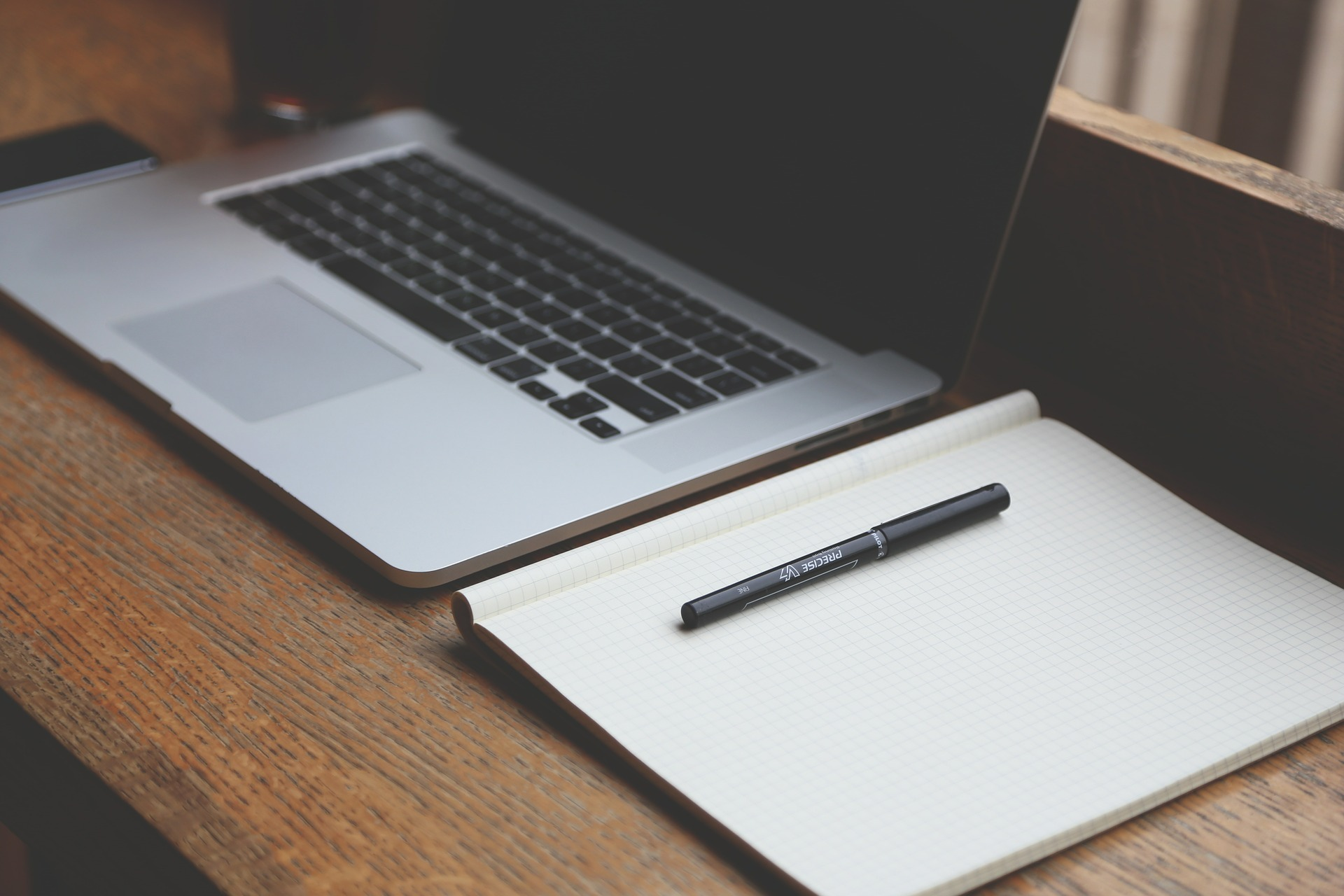 improve your job prospects online courses writing a cv online a laptop notebook and pen on a desk