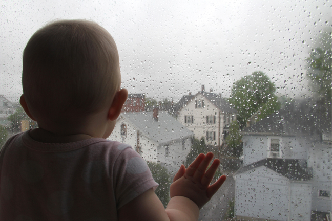 Child staring out of window at rain
