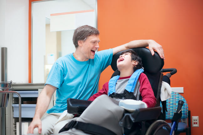 Father talking with disabled son waiting in doctor's office