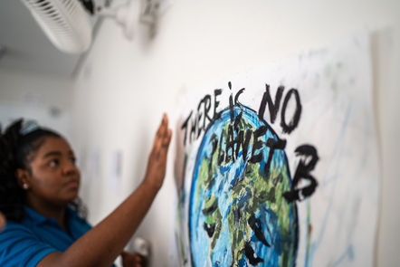 A woman by a painted sign reading 'There is no planet B'