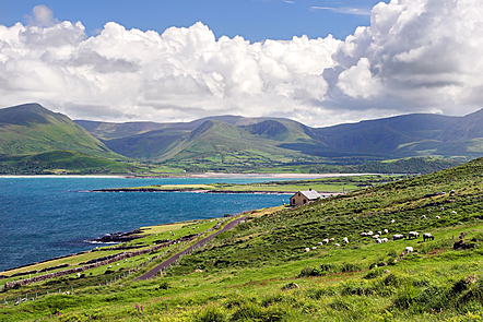 Scenic photo of the Irish coast with a small cottage facing the bright blue bay and tall green mountains in the background.