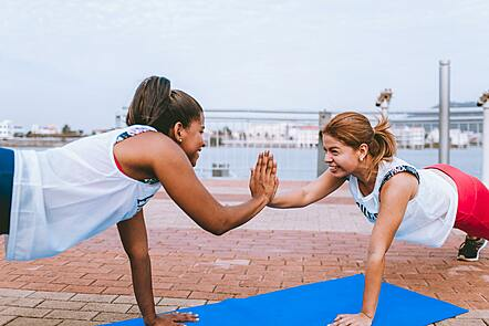 Two women high fiving whilst performing a fitness move called the plank.