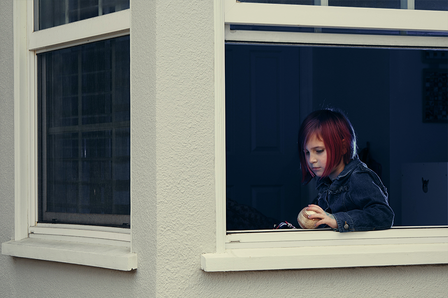 Young girl looking out of a window holding a baseball