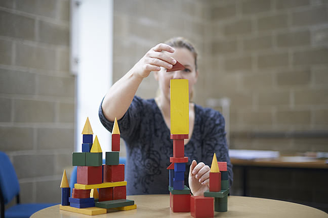 Parent using wooden blocks